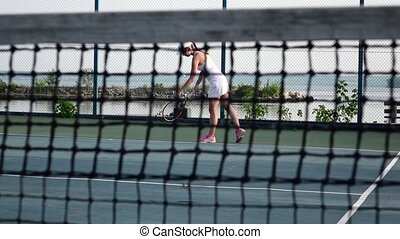 Girl tennis player expecting the tennis ball on court, net in front. Cam moves up