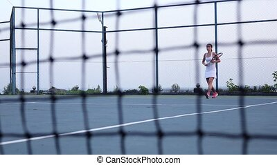 Girl tennis player expecting the tennis ball on court, net in front. Dolly shot