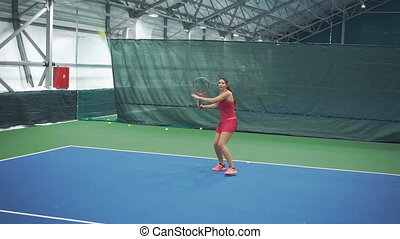 Girl tennis player kicks the ball from her knees