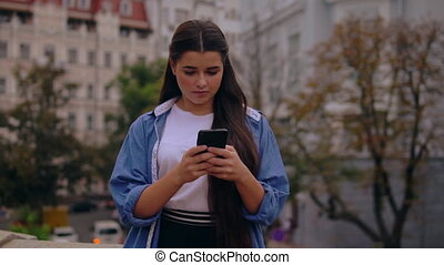 girl texting message on mobile outdoors