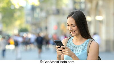 Girl texting messages on phone in the street - Happy girl...