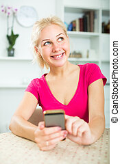 girl texting on mobile phone indoors .
