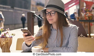 Girl Texts on Phone in Cafe