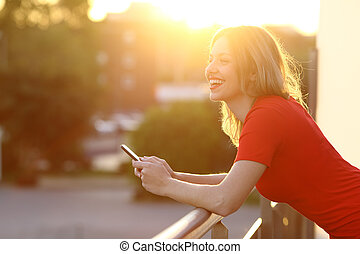 Girl thinking and holding a smart phone at sunset