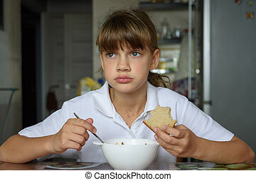 Girl thoughtfully eats soup at the table in the kitchen