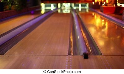 Girl throw bowling ball on middle lane of three in club