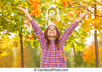 Girl throw maple orange leaves up in autumn park