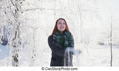 Girl throw up a handful of snow and laughs, sunny winter...