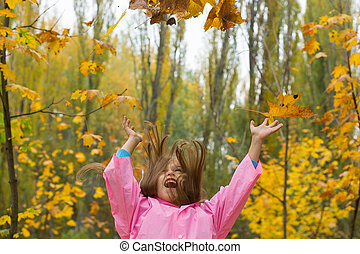 Girl throw yellow leaves up in the park in autumn.