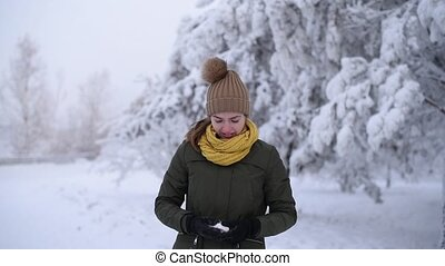 Girl throwing a snowball - Beautiful girl is smiling...
