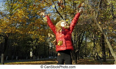 Girl throwing leaves in Autumn in slow motion