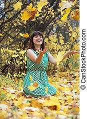 Girl throwing leaves in the air