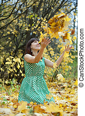 Girl  throwing maple leaves in the air