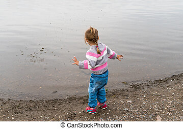Girl throwing stones into the river