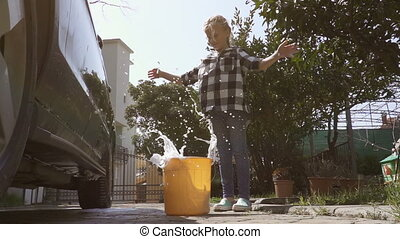 girl throws a sponge in a bucket of soapy water after washing the car