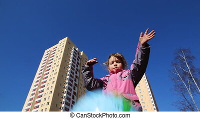 girl throws big beach ball, then he falls down against sky...