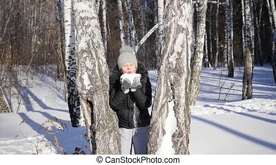 Girl throws snow from behind a tree. winter landscape. sunny day