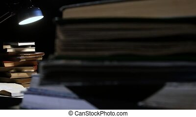Girl thumbs through the book and find information and rejoices. Black background