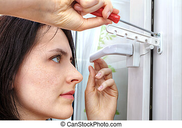 Girl tightens screw securing limiter of opening  plastic window.