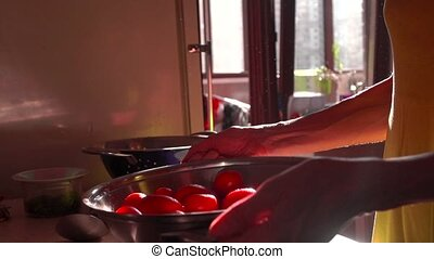 Girl tossing red tomatoes in a pan. Super slow motion video