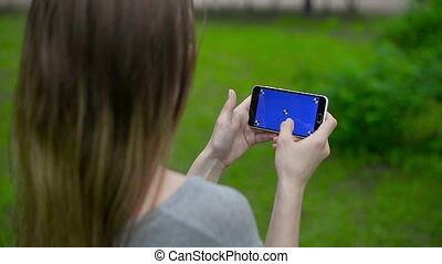 Girl touching a smart phone on green screen with marker