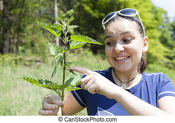 Girl touching stinging nettle leave