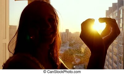 Girl touching the sunlight by hand in her room and makes form of heart at home.