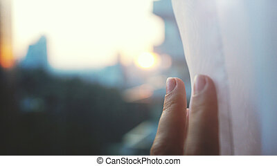 Girl touching the sunlight by hand in her room at home. Female hand opens curtains with view on the city.