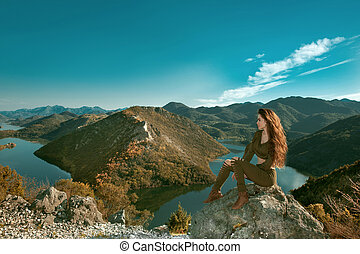 Girl tourist enjoying and sightseeing amazing view of Rijeka Crnojevica, Montenegro. Skadar lake national park, Pavlova Strana. Viewpoint Ridge mountains panoramaic landscape.
