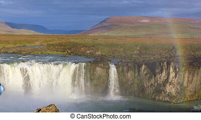 Girl tourist enjoys the view of the Godafoss waterfall
