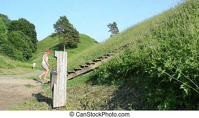 girl tourist hill mound - Young tourist girl climb on mound...