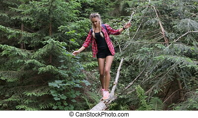 Girl tourist in the woods balances on a fallen tree