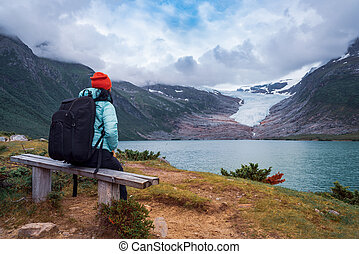 Girl tourist looks at a glacier. Svartisen Glacier in Norway.