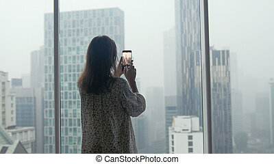 Girl tourist standing at the window and taking photo on a mobile phone view of a skyscraper height in Kuala Lumpur during rain, Malaysia.