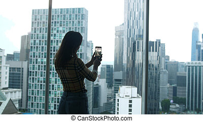 Girl tourist standing at the window and taking photo on a mobile phone view of a skyscraper height in Kuala Lumpur. Malaysia.