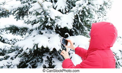 Girl tourist taking photos on the phone of snowy trees in the winter forest