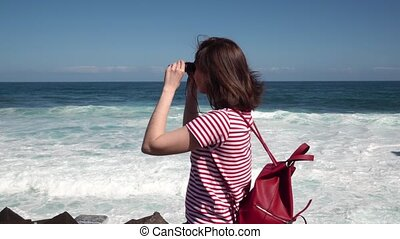 girl tourist walks along the ocean with binoculars