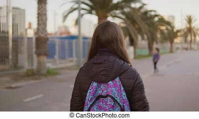 Girl tourist with a backpack on her back walks along the palm promenade