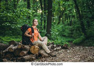 girl tourist with a backpack relax in the woods on logs