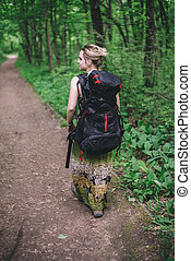 girl tourist with a backpack traveling in the forest