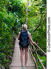 girl tourist with a big backpack in Asia on a wooden trail