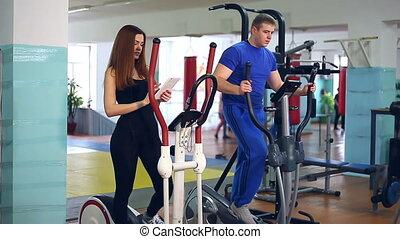 Girl trainer sports man ellipsoid on simulator involved -...