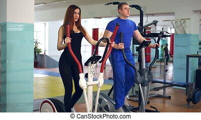 Girl trainer sports man on simulator ellipsoid involved -...