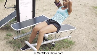 Girl training abs in park - Fit ethnic girl in sportive...