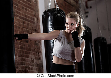 Girl training kick boxing - Horizontal view of girl training...