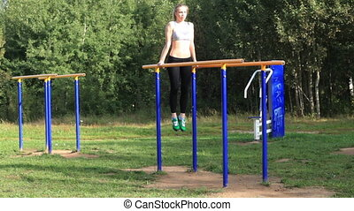 Athletic girl exercising on parallel bars on sports ground on bright summer day.