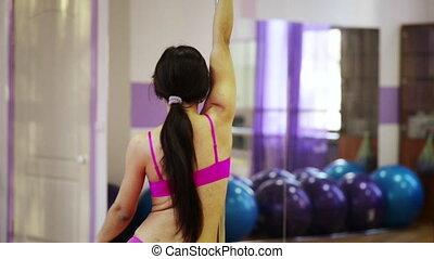 Girl training pole dance in fitness club. - Girl dancing on...