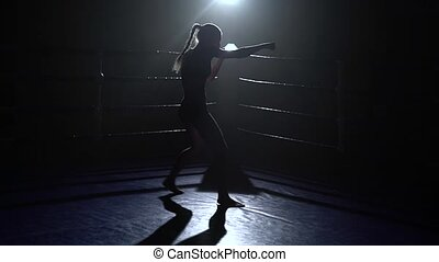 Girl trains, boxing in the ring. silhouette - Girl is...