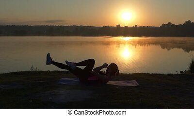 Girl trains her abs at sunset near lake.