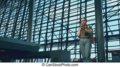 Girl traveler at the airport to talk on a mobile phone -...